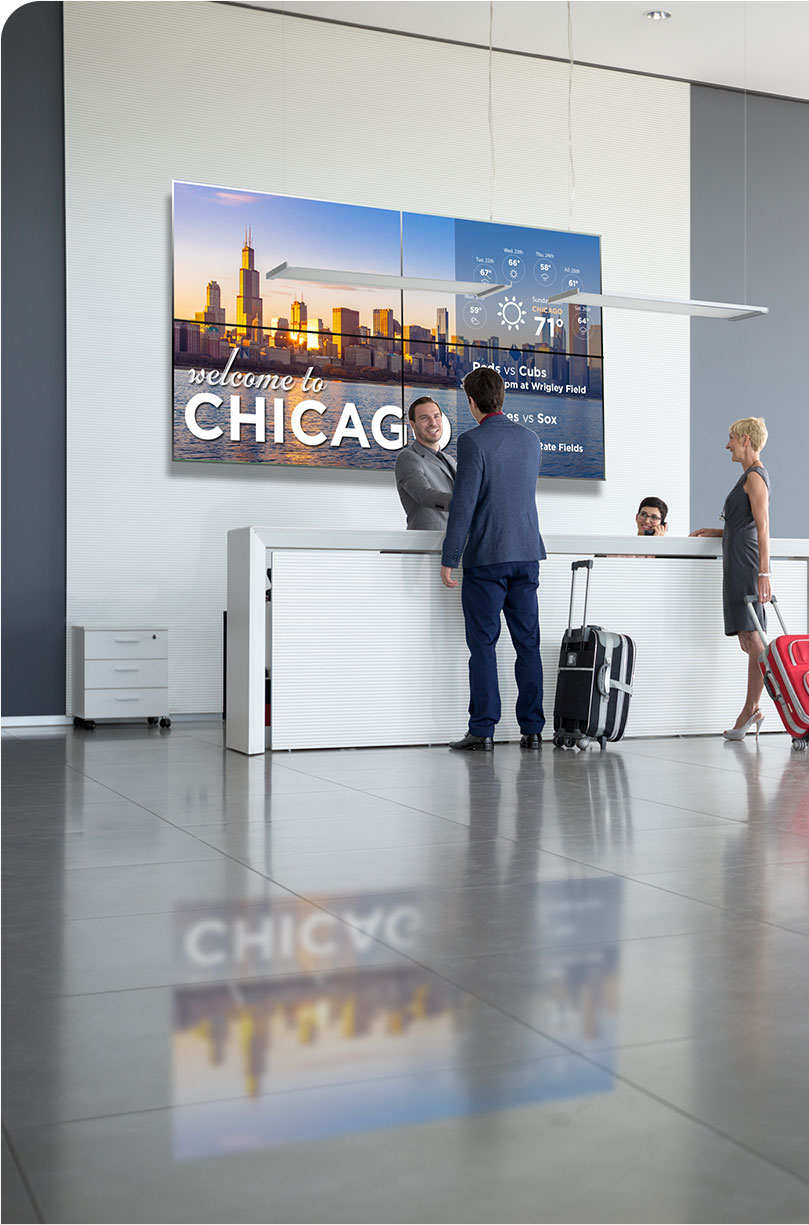 guests in a hotel lobby with digital signage screen